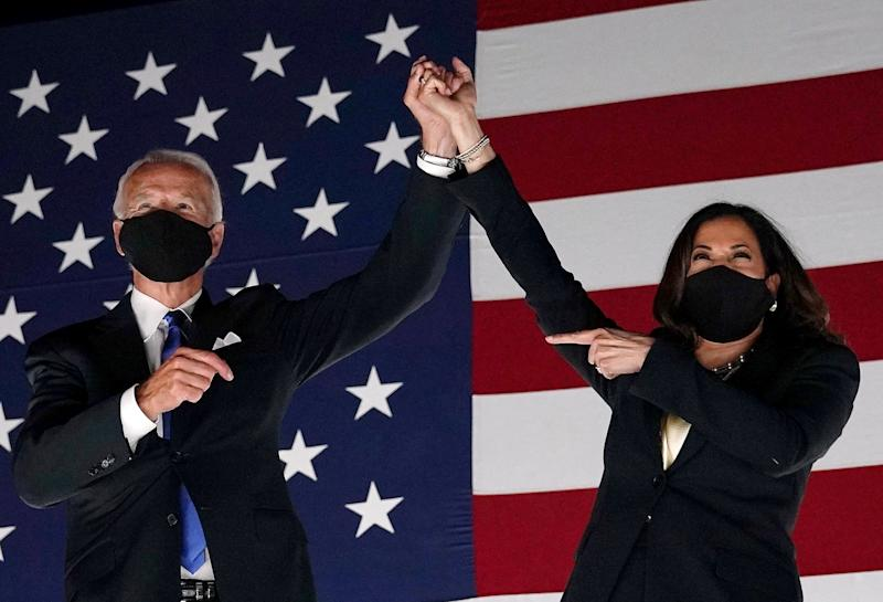 Joe Biden and Kamala Harris raise hands together in front of an American flag