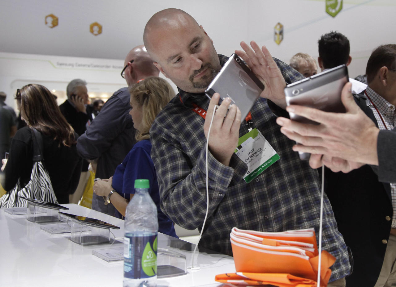 An industry affiliate looks over the Samsung Galaxy Tab 7.7 LTE at the 2012 International Consumer Electronics Show, Wednesday, Jan. 11, 2012, in Las Vegas. (AP Photo/Julie Jacobson)