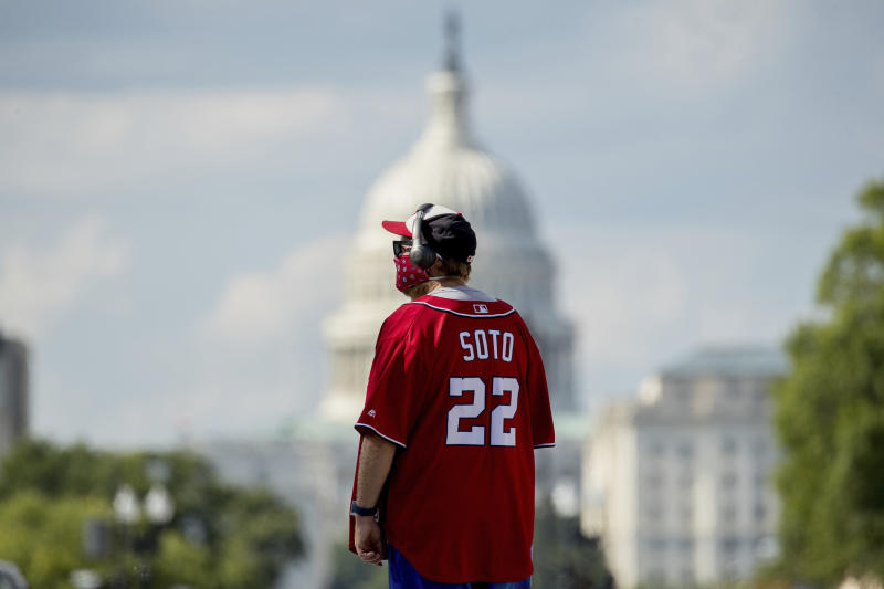 The Dome of the U.S. Capitol is visible as a Washington Nationals fan wearing a Juan Soto jersey walks outside Nationals Park before the New York Yankees and the Washington Nationals play an opening day baseball game, Thursday, July 23, 2020, in Washington. (AP Photo/Andrew Harnik)