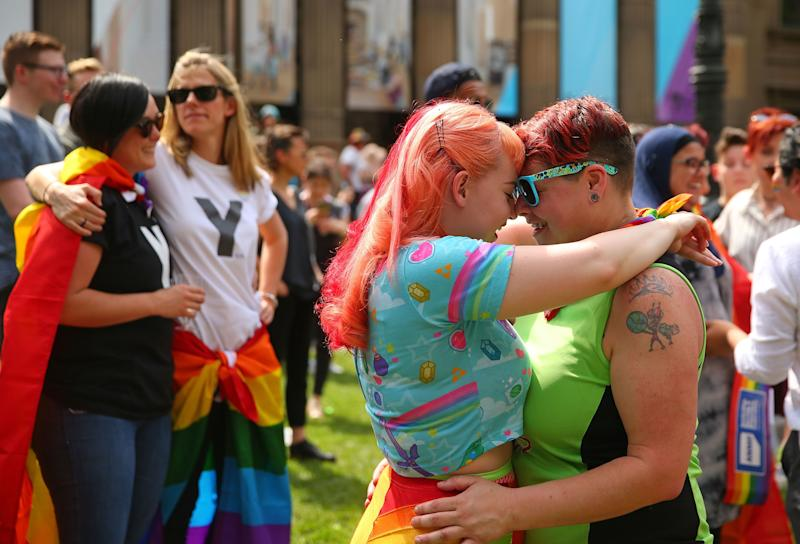 A couple hugs at the gathering at the state library.
