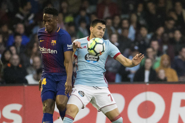 Barcelona's Y. Mina. left, challenges for the ball with RC Celta's Maxi Gomez during a Spanish La Liga soccer match between RC Celta and Barcelona at the Balaidos stadium in Vigo, Spain, Tuesday April 17, 2018. (AP Photo/Lalo R. Villar)