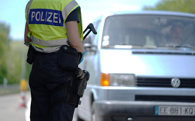 ASTATT, GERMANY - MAY 08: A German border police officer stops cars in a checkpoint of the D87 road at the German-French border during the coronavirus crisis on May 8, 2020 near Rastatt, Germany. The rates of new infections in both Germany and France, as in much of the European Union, have fallen dramatically over recent weeks, allowing governments to ease lockdown measures and strengthening demands by both business leaders and local communities to reopen international borders. In Germany so far Interior Minister Horst Seehofer is resisting a fast-paced lifting of border closures. (Photo by Thomas Niedermueller/Getty Images) - Thomas Niedermueller/Getty Images Europe