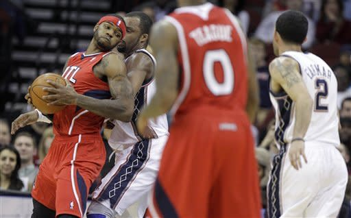 Atlanta Hawks' Josh Smith, left, drives against New Jersey Nets' Shelden Williams as Atlanta Hawks' Jeff Teague (0) and New Jersey Nets' Jordan Farmar (2) look on in the second quarter of an NBA basketball game, Monday, Jan. 9, 2012, in Newark, N.J. (AP Photo/Julio Cortez)