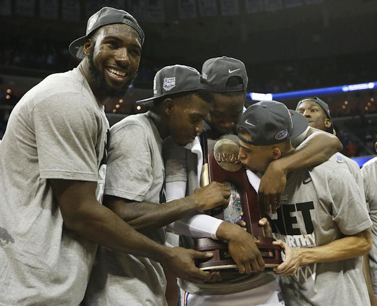 Florida guard Scottie Wilbekin, right, kisses the NCAA trophy standing with team mates after the second half in a regional final game against Dayton at the NCAA college basketball tournament, Saturday, March 29, 2014, in Memphis, Tenn. Florida won 62-52. (AP Photo/Mark Humphrey)