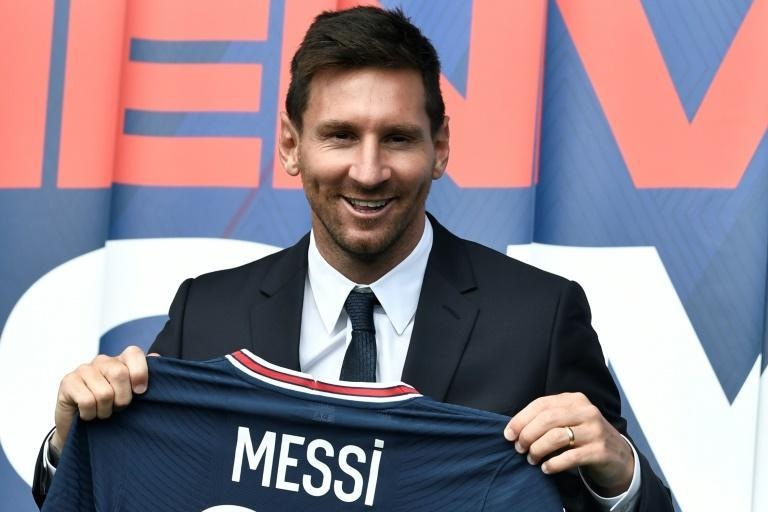 Welcome to Paris: Lionel Messi poses as he holds-up his number 30 shirt