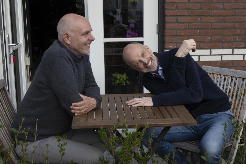 Gert Kasteel, left, and Dolf Pasker, right, one of the first four couples who tied the knot when same-sex marriage was legalized in the Netherlands, react during an interview at their home in Weesp, near Amsterdam, Netherlands, Wednesday, March 31, 2021. Twenty years ago, the mayor of Amsterdam married four couples in City Hall as the Netherlands became the first country in the world with legalized same-sex marriage. It's now legal in 28 countries, including most of Western Europe, as well as in the self-governing island of Taiwan. (AP Photo/Peter Dejong)