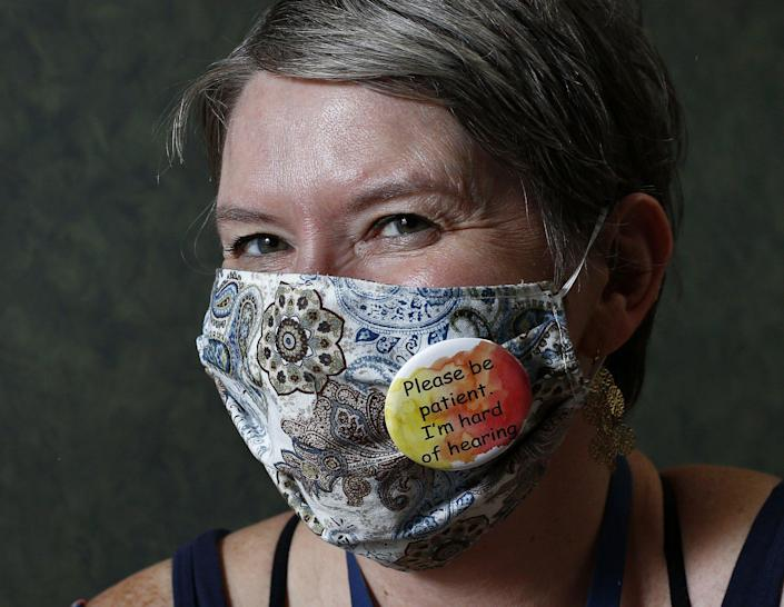 Amy Bull, who is hard of hearing, wears a button on her mask that tells people.