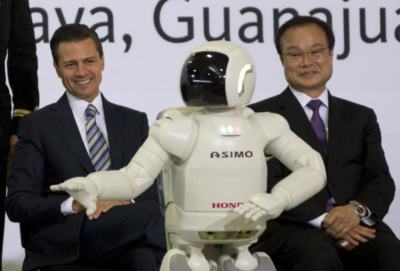 Mexico's President Enrique Pena, left, and Honda Motor and CEO Takanobu Ito watch Hondo's interactive robot Asimo during the inauguration of the new multibillion-dollar Honda car plant in Celaya, in the central Mexican state of Guanajuato, Friday, Feb. 21, 2014. Mexico is on track to overtake Japan and Canada and become the United States' No. 1 source of imported cars by the end of next year, part of a national manufacturing boom that has turned the auto industry into a bigger source of dollars than money sent home by migrants. (AP Photo/Eduardo Verdugo)