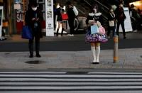 Pedestrians wearing protective masks amid the coronavirus disease (COVID-19) outbreak stand in front of a cross walk at a shopping district in Tokyo