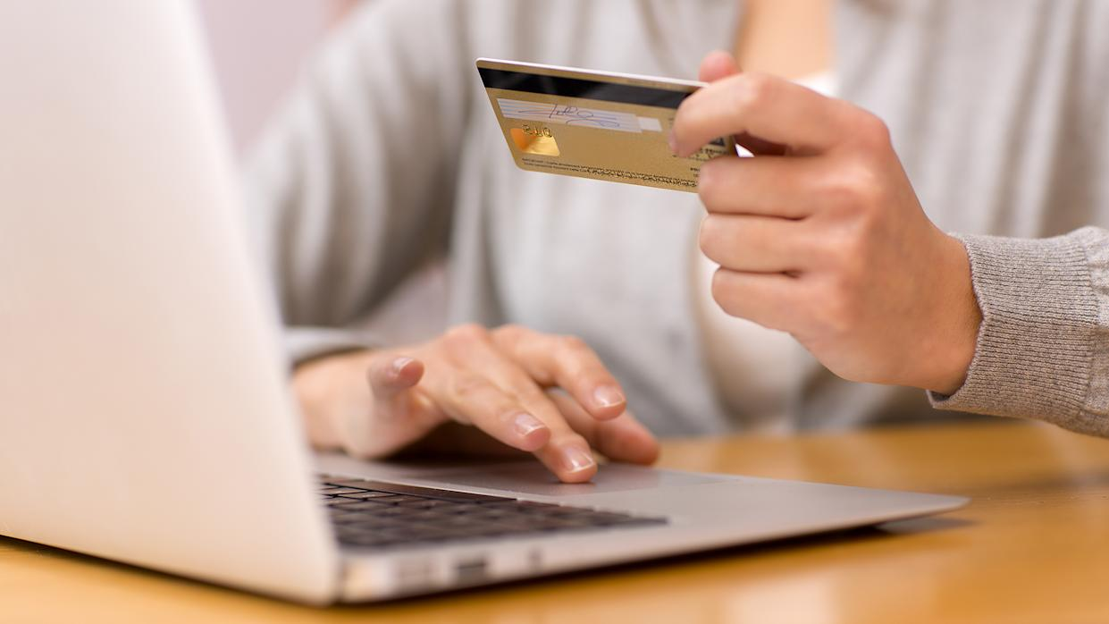 Close-up woman's hands holding a credit card and using computer keyboard for online shopping.