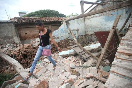Peregrina, 26, an indigenous Zapotec transgender woman also know as Muxe, walks on the debris of her house destroyed after an earthquake that struck on the southern coast of Mexico late on Thursday, in Juchitan