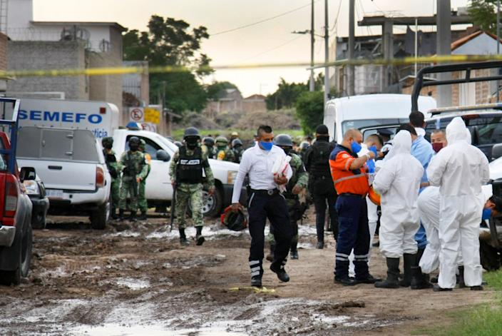 "Forensic service personnel prepare to enter the drug rehabilitation center in Irapuato after the massacre. <span class=""copyright"">(Mario Armas / Associated Press)</span>"