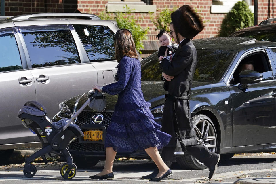 FILE - In this Oct. 4, 2020, file photo, an Orthodox Jewish family crosses a street during the Jewish holiday of Sukkot in the Borough Park neighborhood in the Brooklyn borough of New York. Amid a new surge of COVID-19 in New York's Orthodox Jewish communities, many residents are reviving health measures that some had abandoned over the summer – social distancing, wearing masks. For many, there's also a return of anger: They feel the city is singling them out for criticism that other groups avoid. (AP Photo/Kathy Willens, File)
