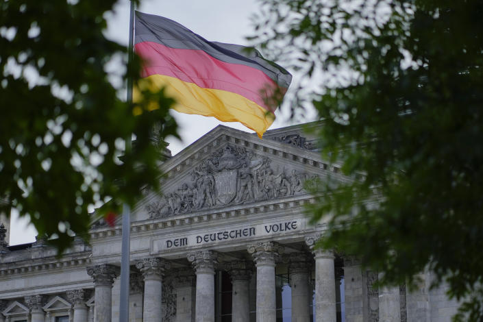 The German national flag waves in front of the German parliament building, the Reichstag Building, with the slogan: 'To The German People' in Berlin, Tuesday, Sept. 28, 2021. Germany's newly elected lawmakers are holding their first meetings as their parties digest the fallout of the election that reduced outgoing Chancellor Angela Merkel's bloc to its worst-ever result and start the process of putting together a new government. (AP Photo/Markus Schreiber)