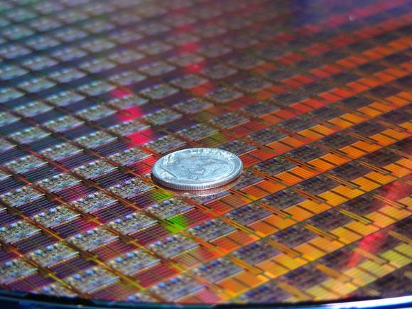 An Intel chip wafer with a dime on it.