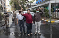 Thai activist Somyot Pruksakasemsuk, left Parit Chiwarak, and Arnon Nampha raise a three-finger salute, a symbol of resistance, as they arrive at the criminal court in Bangkok, Thailand, Tuesday, Feb. 9, 2021. Four activists, including Somyot, Parit, and Arnon, from Thailand's prodemocracy movement reported themselves to the court on Tuesday as they are formally charge of defaming the monarchy, as the authorities step up legal actions against protesters accused of insulting the royal institution. (AP Photo/Sakchai Lalit)