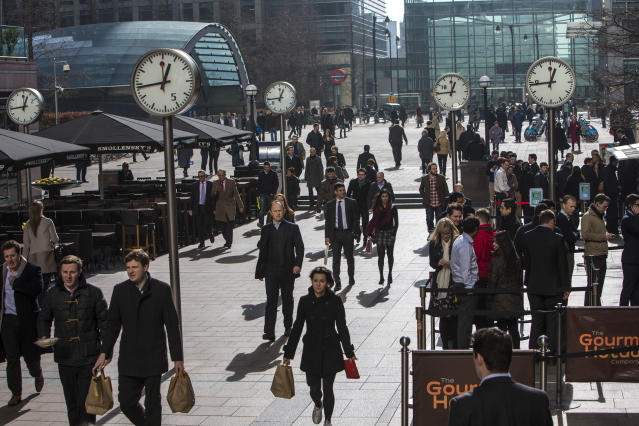 City workers walk under the clocks of Nash Court in Reuters Plaza to commute to work in Canary Wharf financial district London, England, United Kingdom. (In Pictures Ltd./Corbis via Getty Images)