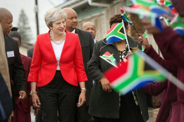 Britain's Prime Minister Theresa May is greeted by schoolchildren waving British and South African flags during a visit to the ID Mkhize Secondary School in Gugulethu township, about 15 km from the centre of Cape Town, on August 28, 2018