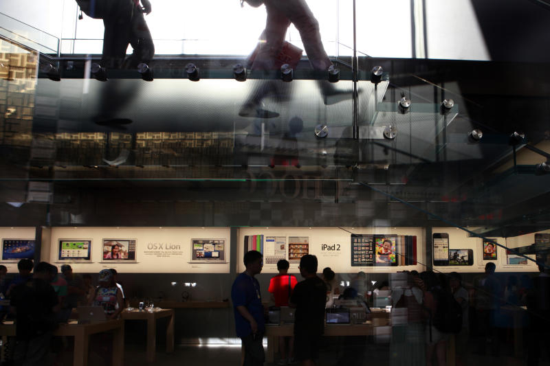 Visitors look at computer products near advertisement for Apple's iPad tablet computer at an Apple store in Beijing, China, Monday, July 2, 2012. Apple agreed to pay $60 million to settle a dispute in China over ownership of the iPad name, a court announced Monday, removing a potential obstacle to sales of the popular tablet computer in the key Chinese market. (AP Photo/Ng Han Guan)