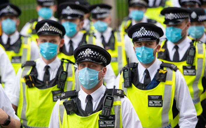Police wearing protective face masks at an Extinction Rebellion protest in Parliament Square, London - Dominic Lipinski/PA
