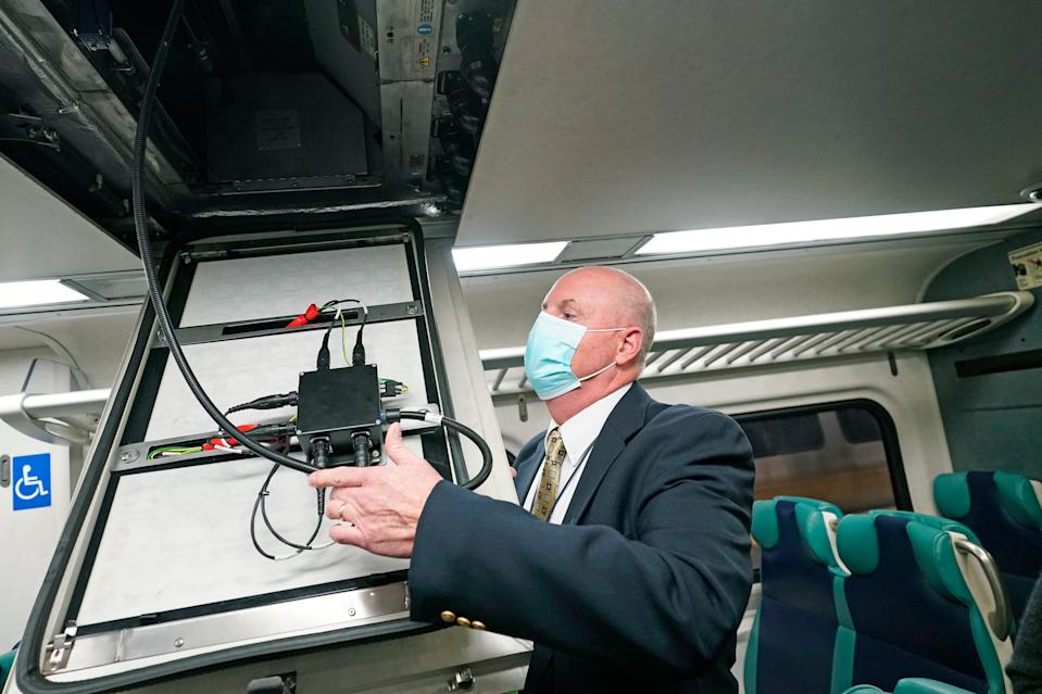 James Heimbuecher, MTA Metro-North Railroad's chief mechanical officer, demonstrates an air purification pilot program designed to remove airborne viruses and bacteria in enclosed spaces on MTA's Metro-North railroad cars, Thursday, Oct. 15, 2020, in New York. The MTA is the first transit agency in North America to test the technology. (AP Photo/Kathy Willens)
