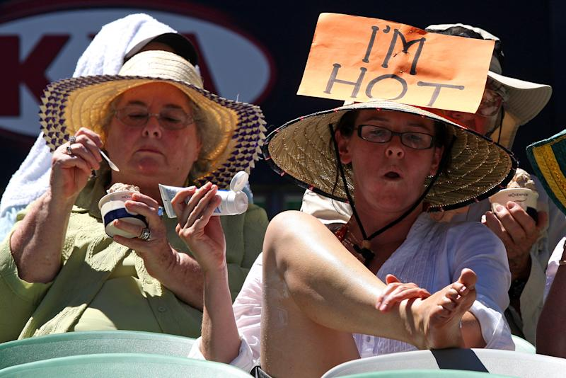 FILE - In this Jan. 28, 2009, file photo, a spectator applies sun cream while others eat ice cream as they try to keep cool in the scorching heat on Rod Laver Arena at the Australian Open tennis tournament in Melbourne, Australia. Top climate scientists are gathering in Japan this week to finish up a report on the impact of global warming. And they say if you think climate change is only faced by some far-off polar bear decades from now, well, you're mistaken. They say the dangers of a warming Earth are immediate and human. The report says risks from warming-related extreme weather are at the moderate level now, but are likely to become high with just a bit more warming. While it doesn't say events were caused by climate change, the report mentions heat waves in Australia. (AP Photo/Rick Stevens, File)