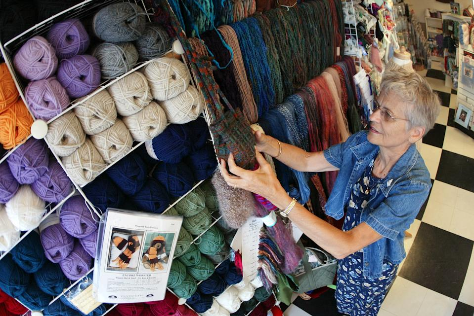 DES PLAINES, IL - JULY 26:  Sixty-eight-year-old Barb Blume arranges yarn at the Mosaic Yarn Studio July 26, 2002 in Des Plaines, Ilinois. Blume is a retired nurse who turned her hobby of knitting into a second career at the yarn studio where she is the assistant manager and knitting class instructor.  (Photo by Tim Boyle/Getty Images)