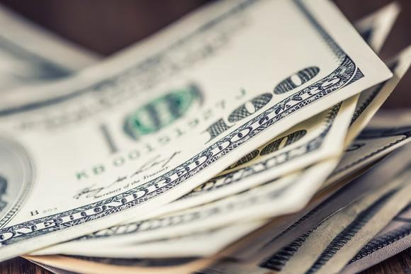 A close-up of a stack of $100 bills.