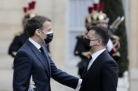 French President Emmanuel Macron, left, welcomes Ukrainian President Volodymyr Zelenskyy at the Elysee palace in Paris, Friday, April 16, 2021. Ukrainian President Volodymyr Zelenskyy is holding talks with French President Emmanuel Macron and German Chancellor Angela Merkel amid growing tensions with Russia, which has deployed troops at the border with the country. (AP Photo/Lewis Joly)