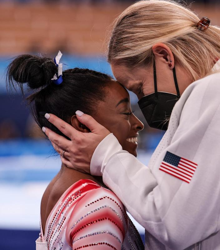 Simone Biles is embraced by Cecile Landi.