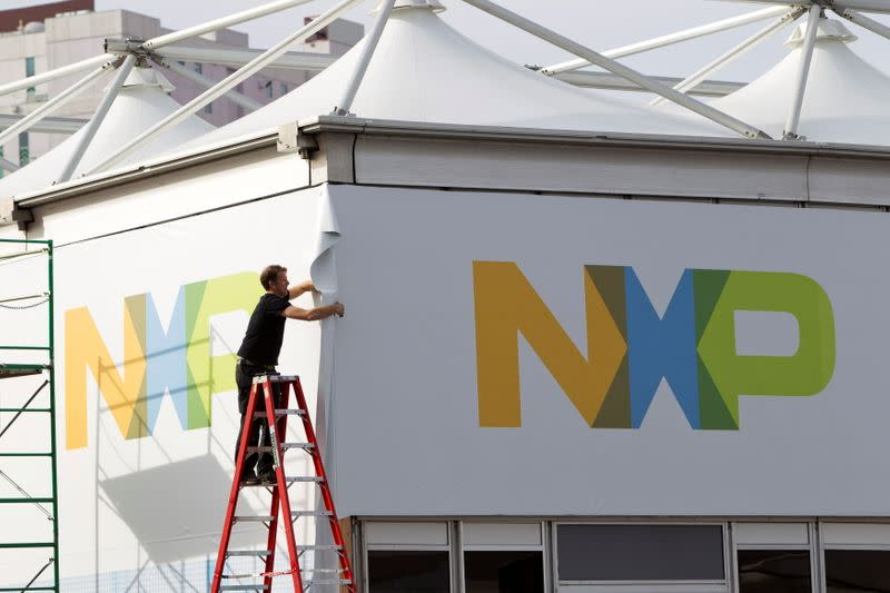 FILE PHOTO: A man works on a tent for NXP Semiconductors in preparation for the 2015 International Consumer Electronics Show (CES) at Las Vegas Convention Center in Las Vegas