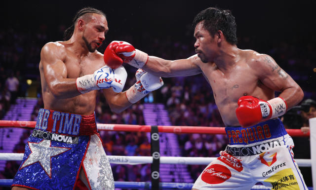 Manny Pacquiao, right, exchanges punches with Keith Thurman in the seventh round during a welterweight title fight Saturday, July 20, 2019, in Las Vegas. (AP Photo/John Locher)