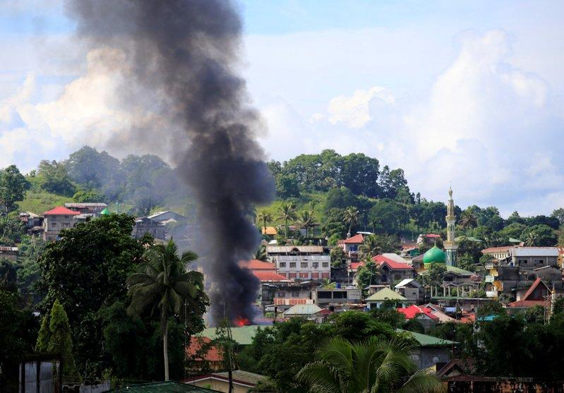 Smoke billowing from a burning building is seen as government troops continue their assault on insurgents from the Maute group, who have taken over large parts of Marawi City. REUTERS/Romeo Ranoco