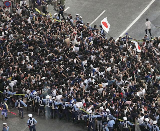 Police officers try to control Japanese soccer fans who gathered at an intersection after they celebrate the victory after the World Cup Group H soccer match Colombia vs Japan, at Shibuya district in Tokyo, Japan, in this photo take by Kyodo from the glass wall of 'MAGNET by Shibuya 109', June 19, 2018. Mandatory credit Kyodo/via REUTERS ATTENTION EDITORS - THIS IMAGE WAS PROVIDED BY A THIRD PARTY. MANDATORY CREDIT. JAPAN OUT. NO COMMERCIAL OR EDITORIAL SALES IN JAPAN.