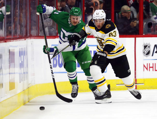 Boston Bruins' Brad Marchand (63) eyes the puck after battling Carolina Hurricanes' Lucas Wallmark (71) for position during the first period of an NHL hockey game, Sunday, Dec. 23, 2018, in Raleigh, N.C. (AP Photo/Karl B DeBlaker)
