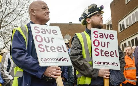 Workers stand with signs at Tata steel works - Credit: WPA Pool/Getty Images