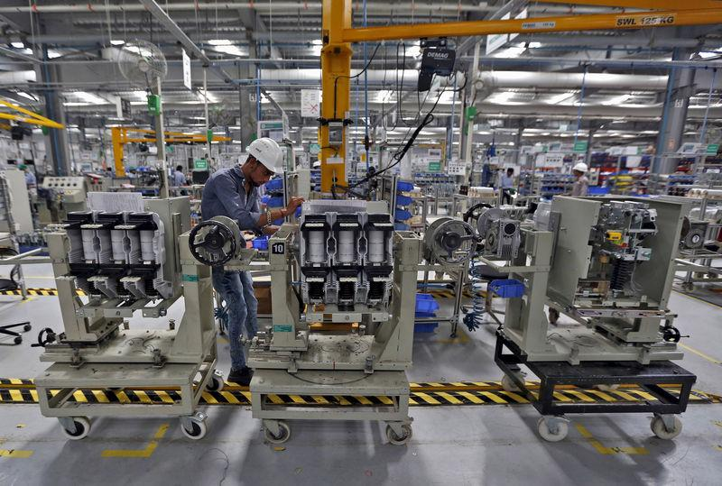 FILE PHOTO: An employee assembles medium voltage switchgears inside the plant of Schneider Electric Infrastructure Ltd. on the outskirts of Vadodara in Gujarat