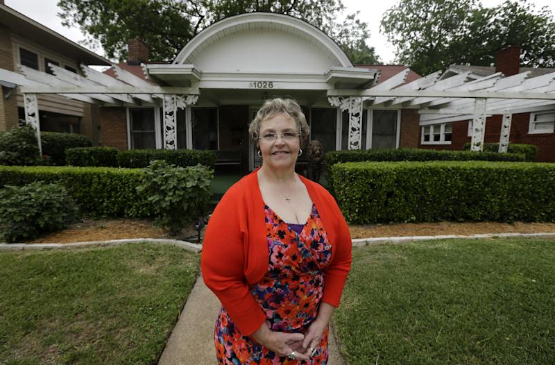 In this May 15, 2013 photo, Patricia Hall poses for photos in front of 1026 North Beckley Avenue, her family's boarding house where Lee Harvey Oswald lived for about six weeks in 1963, in Dallas. Oswald rented a 5-by-14 foot room on Oct. 14, 1963, from Hall's grandmother, Gladys Johnson. He stayed at the red brick house with white trim during the week while working his new job at the Texas School Book Depository, and on the weekends he returned to the suburb of Irving where his wife lived. Hall said she's been considering selling the house for years, but decided the time was right as this year marks the 50th anniversary of Kennedy's assassination in downtown Dallas. (AP Photo/Tony Gutierrez)