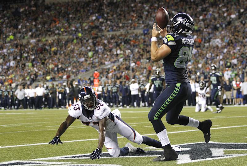 Seattle Seahawks tight end Sean McGrath (84) bobbles a pass before pulling it down for a touchdown as Denver Broncos' Duke Ihenacho (33) looks on in the first half of a preseason NFL football game, Saturday, Aug. 17, 2013, in Seattle. (AP Photo/John Froschauer)