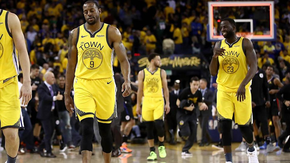 The Warriors walk off the court dejected. (Photo by Ezra Shaw/Getty Images)