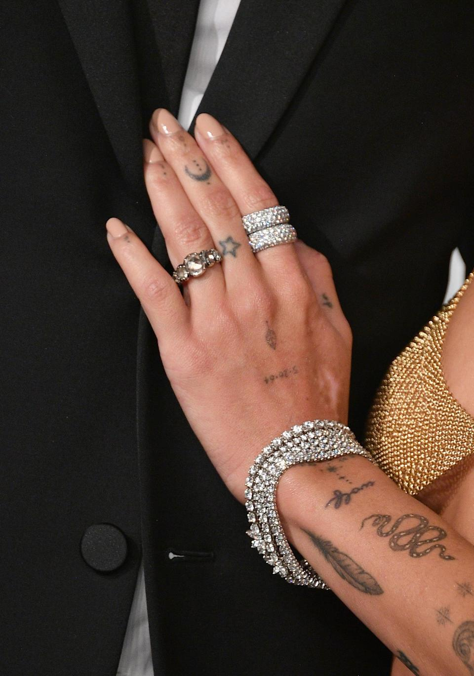 """<p>Starting in 2016, Kravitz added a few more pieces to her left hand, including her father's birthday, 5.26.64, the outline of a star on her middle finger, a red heart on the inside of her middle finger, and the word """"up"""" on the inside of her thumb.</p>"""