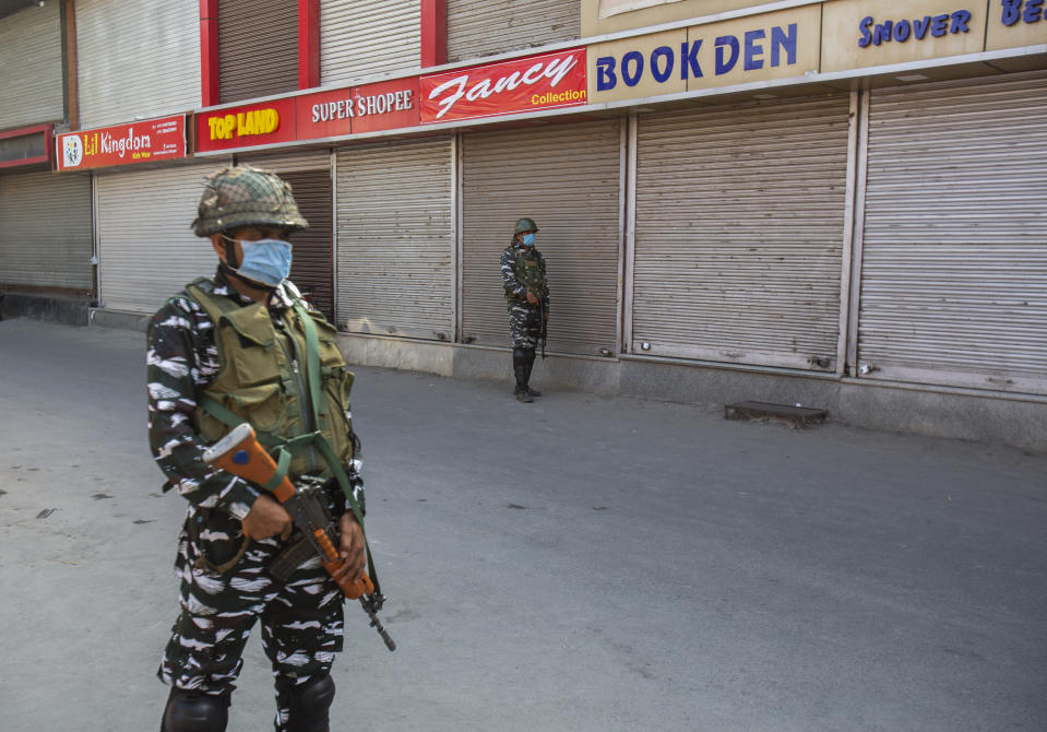 Indian paramilitary soldiers guard at a closed market in Srinagar, Indian controlled Kashmir, Sunday, Sept. 5, 2021. Authorities Sunday eased some restrictions that had been imposed after the death of top resistance leader Syed Ali Geelani. However, most shops and businesses stayed closed as government forces patrolled roads and streets in the city. (AP Photo/Mukhtar Khan)