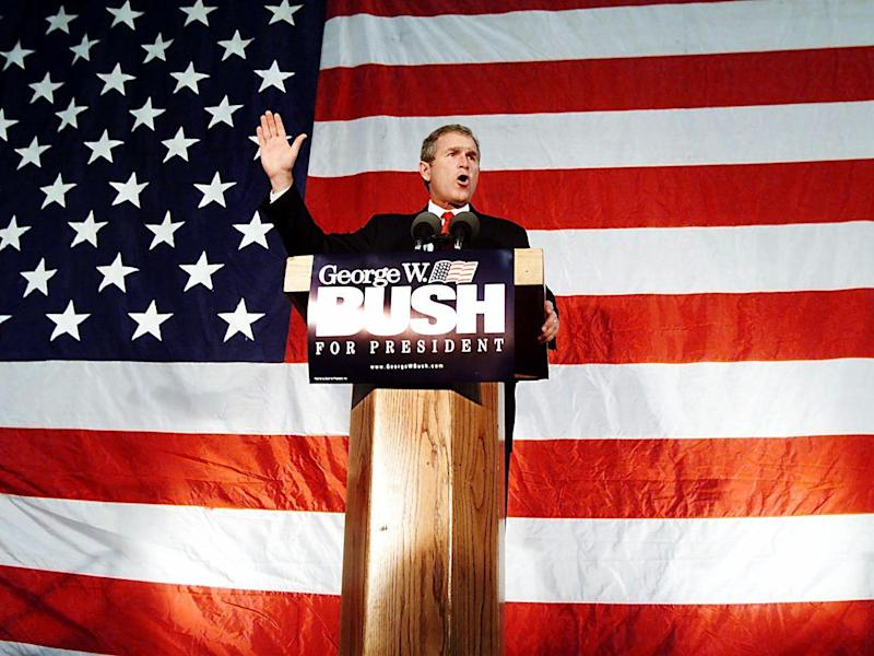 Republican presidential hopeful Texas Governor George W. Bush speaks in front of an American flag during a rally for the Cedar Rapids Community 22 January 2000 in Cedar Rapids, Iowa. Bush is campaigning in the state before the 24 January 2000 Iowa caucus.