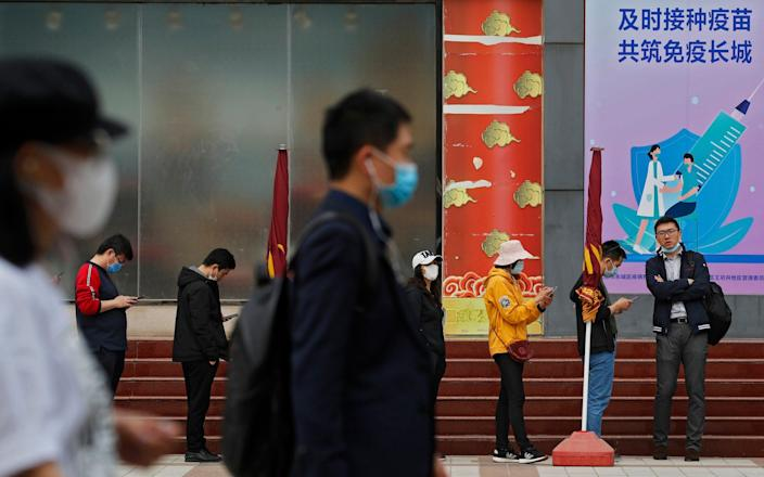 """Residents line up for their jab at a vaccination site with a board displaying the slogan """"Timely vaccination to build the Great Wall of Immunity together"""" in Beijing - Andy Wong/AP"""