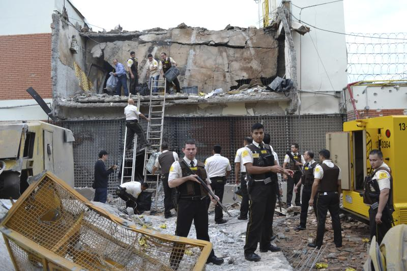 Guards and police inspect a vault that the assailants blew up early morning in Ciudad del Este, Paraguay, Monday, April 24, 2017. Dozens of attackers armed with assault rifles used explosives to blast open the vault of an armored car company early Monday and apparently escaped by boat into Brazil with a haul of cash, authorities said. (Mariana Ladaga/Diario ABC Color via AP)