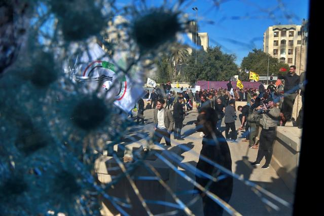 Shiite militia supporters are seen through a broken window of a checkpoint in front of the U.S. Embassy in Baghdad on Dec. 31. (Photo: Khalid Mohammed/AP)