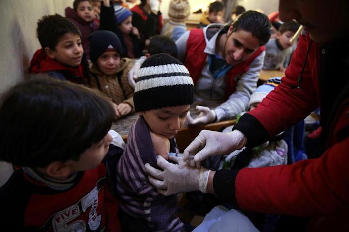 Members of the Syrian Arab Red Crescent administer vaccinations to children at a school in the rebel-held city of Douma, north-east of the Syrian capital Damascus, on March 21, 2016 (AFP Photo/Abd Doumany)
