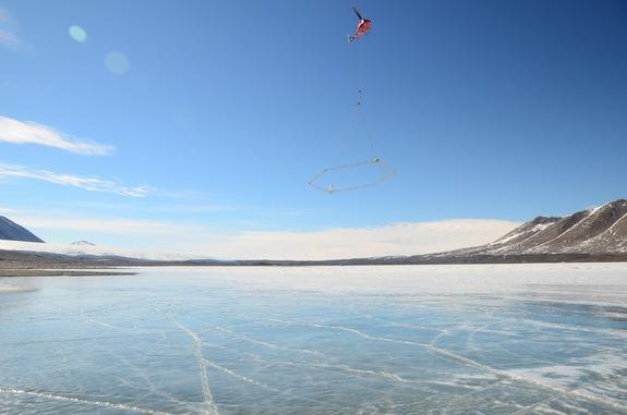 A helicopter flies a transmitter across Lake Frxyell, Antarctica.