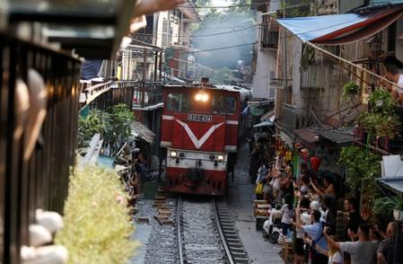Tourists take photos as a train comes down the track along a street in the Old Quarter of Hanoi, Vietnam