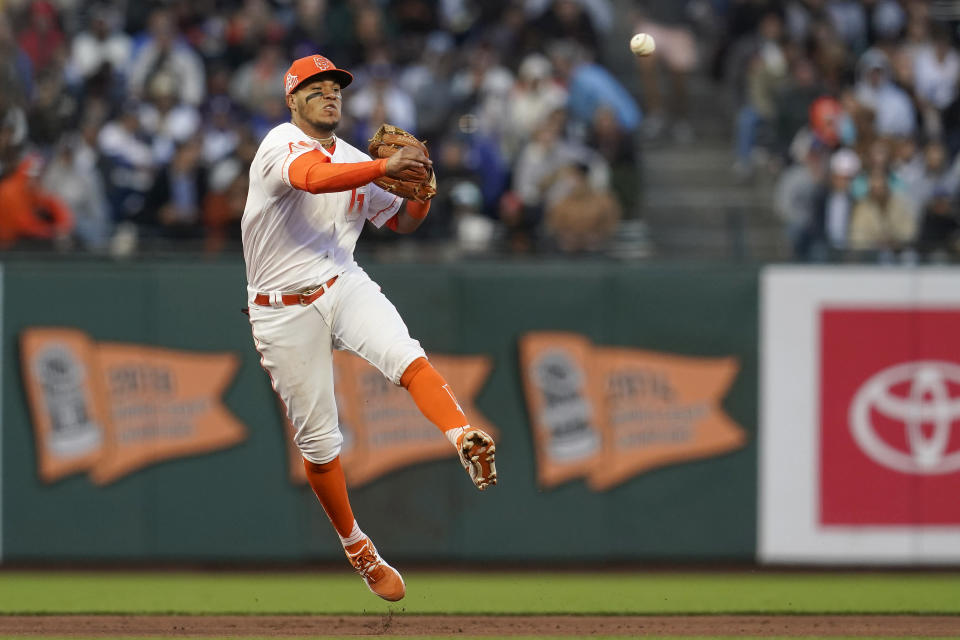 San Francisco Giants shortstop Thairo Estrada throws out Los Angeles Dodgers' Chris Taylor at first base during the sixth inning of a baseball game in San Francisco, Tuesday, July 27, 2021. (AP Photo/Jeff Chiu)